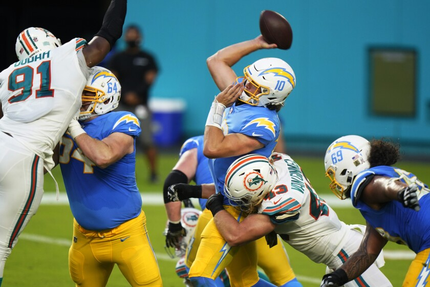 Chargers quarterback Justin Herbert (10) attempts to throw a pass under pressure from Miami Dolphins defense,