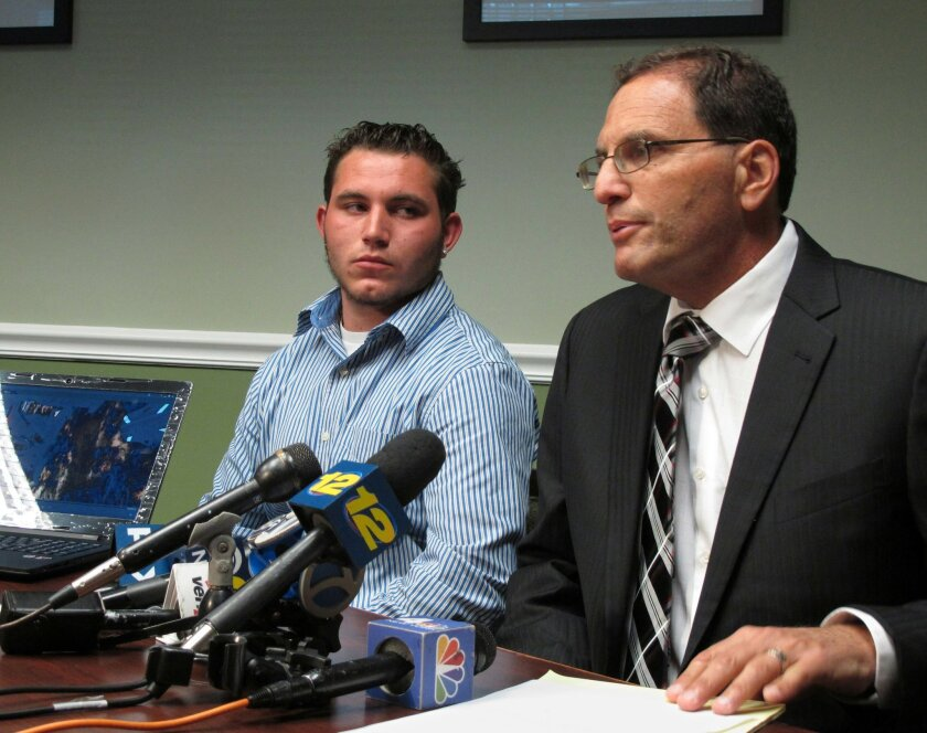 FILE - In this Aug. 5, 2015 file photo, Thomas Demint, left, listens to his attorney Kenneth Mollins at a news conference in Hauppauge, N.Y., after police arrested Demint when he took a cellphone video of police officers arresting two of his friends, and body-slamming their mother. Demint says three officers tackled him, took away his smartphone and tried, unsuccessfully, to erase the video before arresting him on charges of obstruction of governmental administration and resisting arrest. Civil liberties experts say Demint is part of a growing trend of citizen videographers getting arrested after trying to record police behavior. (AP Photo/Frank Eltman, File)