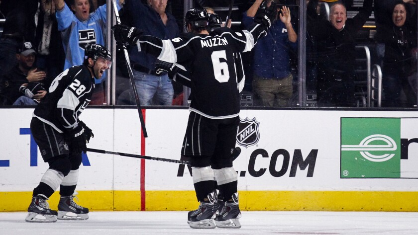 Kings center Jarret Stoll, left, celebrates with teammate Jake Muzzin after scoring in overtime to lift the Kings to a 3-2 win over the Ducks on Saturday.