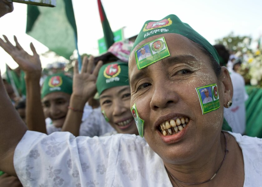Supporters of Myanmar's military backed Union Solidarity and Development Party (USDP) with stickers of President Thein Sein on their facess dance during an election campaign event in Yangon, Myanmar, Friday, Nov. 6, 2015. On Sunday Myanmar will hold what is being viewed as the country's best chance