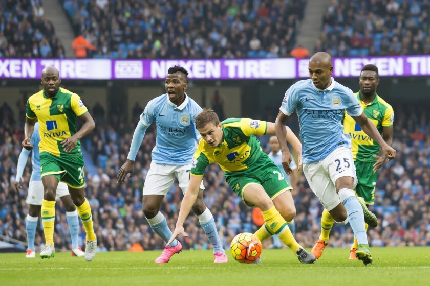 Manchester City's Fernandinho, second right, takes the ball past Ryan Bennett of Norwich City, bottom centre, during the English Premier League soccer match between Manchester City and Norwich at the Etihad Stadium, Manchester, England, Saturday Oct. 31, 2015. (AP Photo/Jon Super)