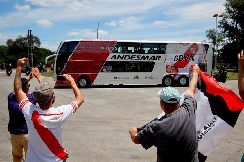 Hinchas de River Plate saludan al autobús que traslada a los jugadores de su equipo hacia el avión con destino a Madrid hoy, para jugar la final de laCopa Libertadores ante el Boca Juniors, en Ezeiza, Buenos Aires (Argentina). EFE