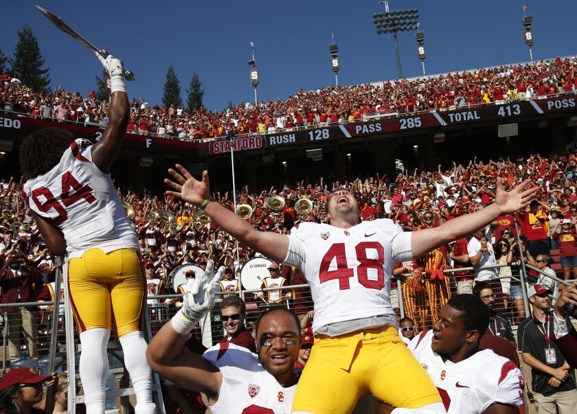 USC kicker Andre Heidari celebrates on the shoulders of teammates Soma Vainuku, left, and Juju Smith as defensive lineman Leonard Williams conducts the band after the Trojans' victory over Stanford on Sept. 6, 2014.