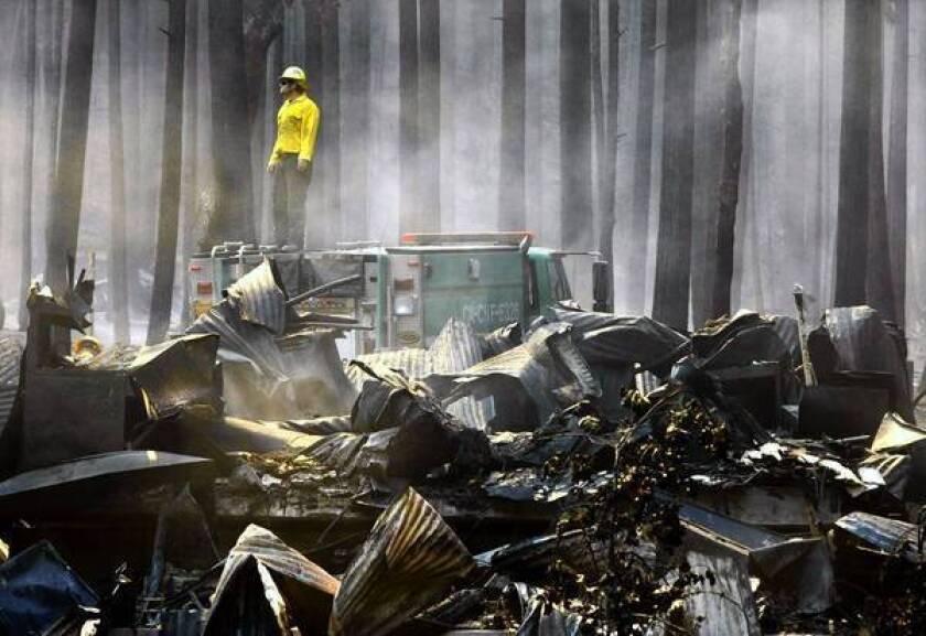 A firefighter surveys the smoldering ruins of the 1922 Berkeley Tuolumne Camp near Groveland, Calif.