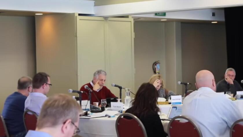 CalPERS board member Bill Slaton, in red sweater, launches his attack on fellow member J.J. Jelincic, far right, during a Jan. 19 meeting in Monterey.