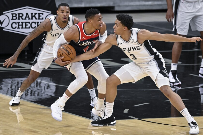 Washington Wizards' Russell Westbrook, center, fights to keep possession as he is defended by San Antonio Spurs' Keldon Johnson (3) and Dejounte Murray during the first half of an NBA basketball game, Sunday, Jan. 24, 2021, in San Antonio. (AP Photo/Darren Abate)