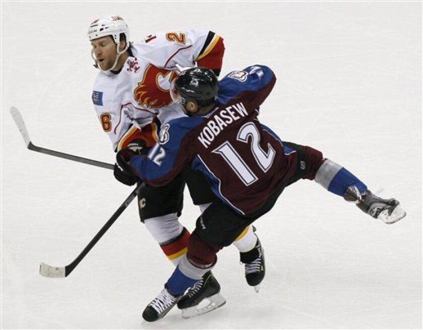 Colorado Avalanche right wing Chuck Kobasew, front, collides with Calgary Flames defenseman Dennis Wideman while pursuing the puck during the first period of an NHL hockey game in Denver on Thursday, Feb. 28, 2013. (AP Photo/David Zalubowski)