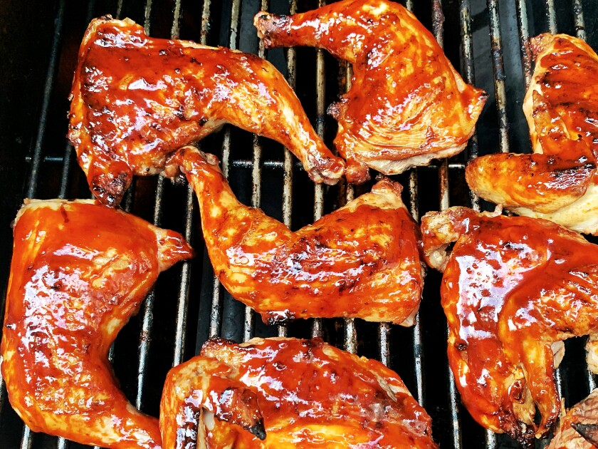 Gochujang-glazed chicken on the grill.
