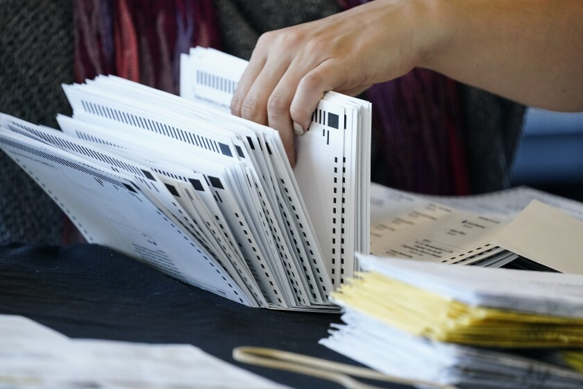 An election worker handles ballots as vote counting in the general election continues in Atlanta.