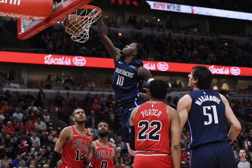 Dallas Mavericks' Dorian Finney-Smith (10) dunks during the first half of an NBA basketball game against the Chicago Bulls, Monday, March 2, 2020, in Chicago. (AP Photo/Paul Beaty)
