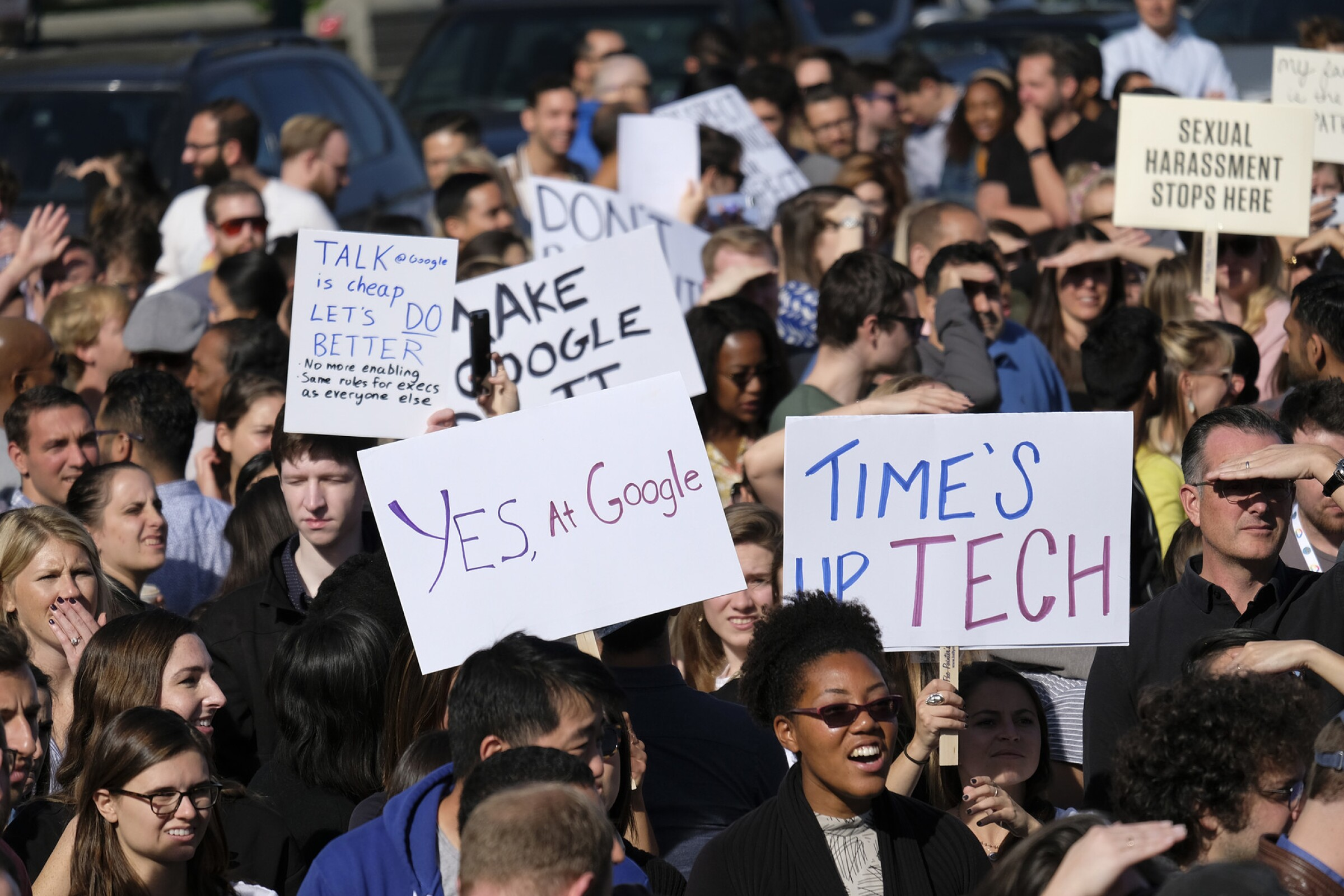 Google employees hold up signs at Harry Bridges Plaza during a walkout Thursday, Nov. 1, 2018, in San Francisco. Several thousand Google employees around the world briefly walked off the job Thursday in a protest against what they said is the tech company's mishandling of sexual misconduct allegations against executives.