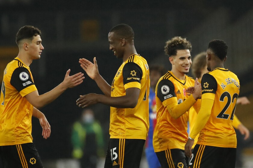 Wolverhampton Wanderers' players shake hands at the end of the English Premier League soccer match between Wolverhampton Wanderers and Crystal Palace at the Molineux Stadium in Wolverhampton, England, Friday, Oct, 30, 2020. (Andrew Boyers/Pool via AP)