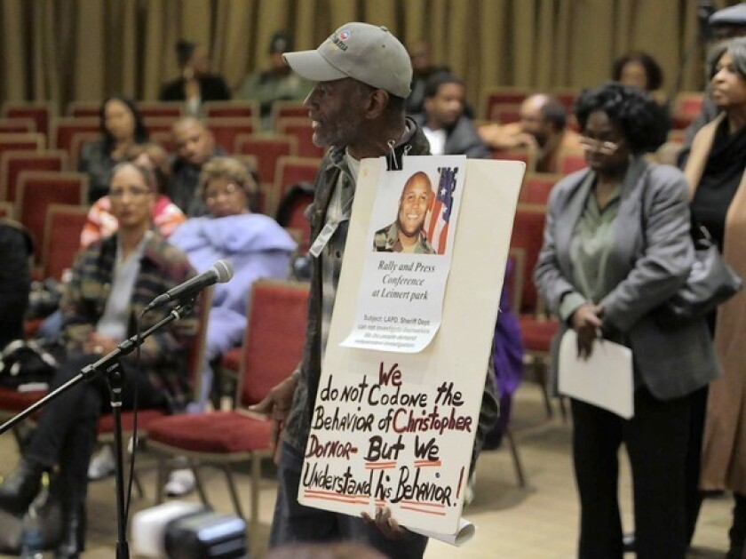 Community activist Morris Griffin holds a sign that echoed sentiments among some audience members at a community meeting in South L.A. in which residents could speak with LAPD Chief Charlie Beck about the department and Christopher Dorner's manifesto blaming his firing from the department on racists.