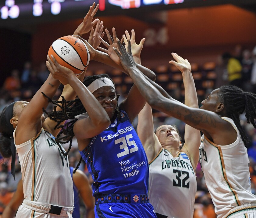 Connecticut Sun forward Jonquel Jones (35) works between New York Liberty defenders Betnijah Laney, left, Sami Whitcomb (32) and Natasha Howard during the first half of a WNBA basketball game Wednesday, Sept. 15, 2021, in Uncasville, Conn. (Sean D. Elliot/The Day via AP)