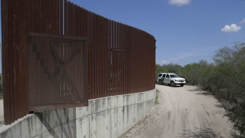 In this Aug. 11, 2017, photo, a U.S. Customs and Border Protection vehicle passes by a section of the border wall in Hidalgo, Texas.