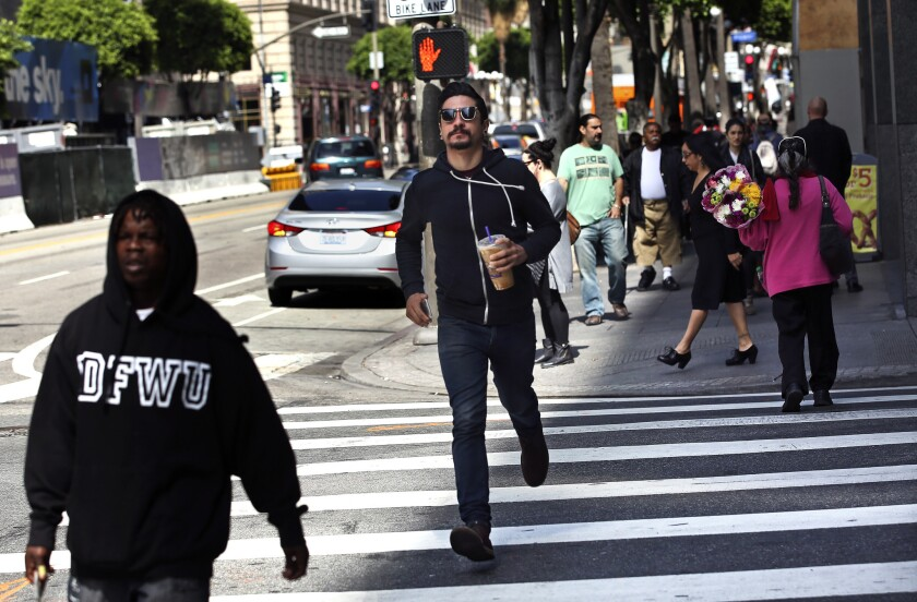As the light flashes red, a pedestrian dashes along the crosswalk at Hope Street and 7th Street in downtown Los Angeles.