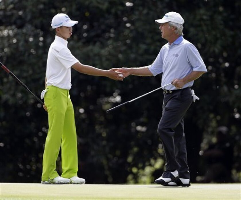 Ben Crenshaw, right, hands a golf ball to Amateur Tianlang Guan, of China, on the 11th hole during a practice round for the Masters golf tournament Monday, April 8, 2013, in Augusta, Ga. (AP Photo/Darron Cummings)