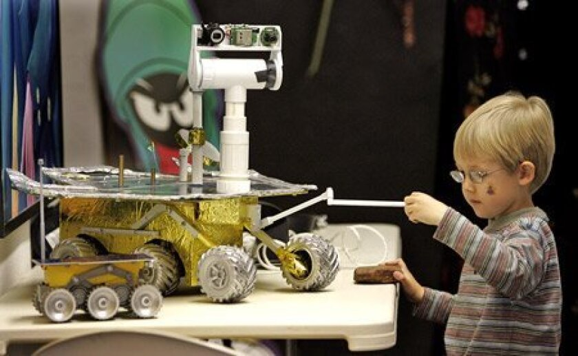 Ben Radcliff, 5, examined a one-quarter-scale model of the rovers exploring Mars. Ben's father is secretary of the San Diego Space Society, which is preparing for next month's science expo in Balboa Park. (Laura Embry / Union-Tribune)
