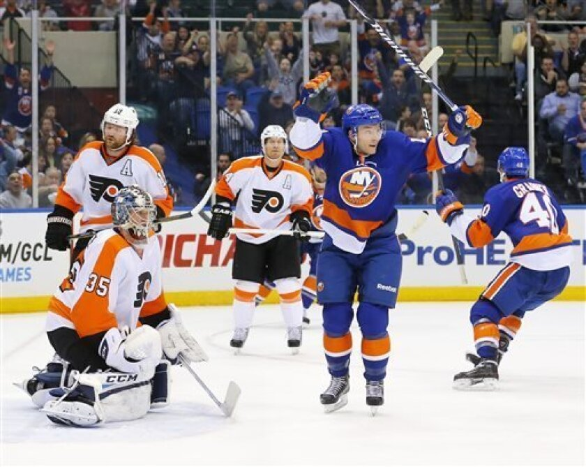 New York Islanders center Keith Aucoin (10) raises his arms to celebrate a goal by Michael Grabner (40) as Philadelphia Flyers goalie Steve Mason (35) looks down during the second period of an NHL hockey game in Uniondale, N.Y., Tuesday, April 9, 2013. (AP Photo/Paul J. Bereswill)