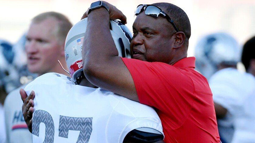 Howard coach Mike London embraces defensive back Aaron Walker before the start of their game against UNLV on Saturday night.