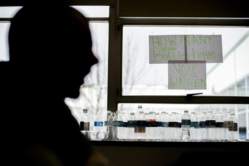 """Water bottles line a window of a classroom with a sign that reads """"How many water bottles have you wasted?"""" as students listen to NFL players Justin Forsett, running back for the Baltimore Ravens, and Torrey Smith, wide receiver for the San Francisco 49ers, who joined Flint Southwestern students as"""