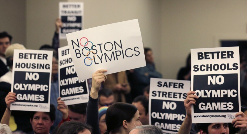 People in the audience hold up placards against the Olympic Games coming to Boston during a public forum regarding the city's 2024 Olympic bid.