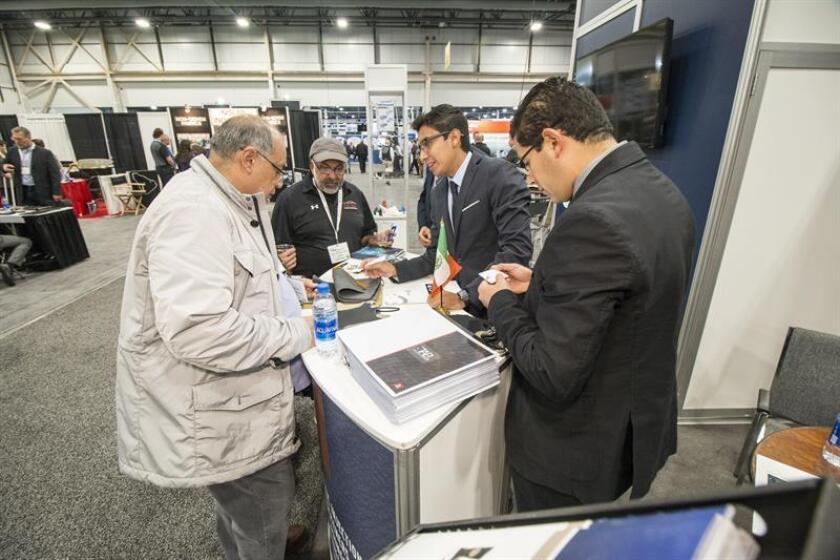 El coordinador de la promoción del sector automotriz en la Coordinadora de Fomento al Comercio Exterior de Guanajuato (Cofoce), Alan orozco (c d), habla con un visitante de la Feria de Interiores del Automóvil hoy, miércoles 24 de octubre de 2018, en Novi, Michigan (EE.UU.). EFE