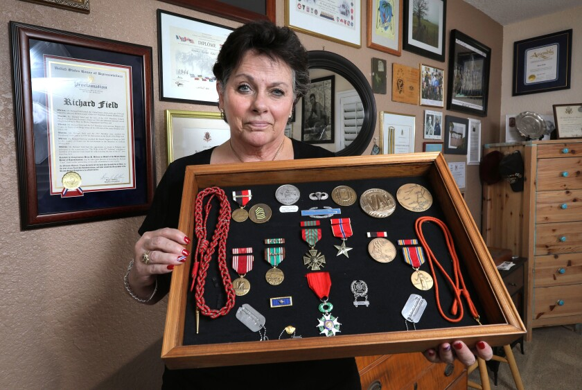 """Portrait of Ginni Field holding the military medals of her World War II veteran father Richard """"Dick"""" Field. On the wall behind her are some of his many awards and honors."""