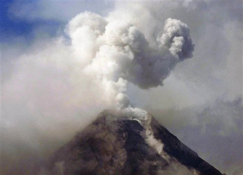 FILE - In this Dec. 23, 2009 file photo, a column of ash shoots up to the sky in a mild eruption of the cloud-covered Mayon volcano as viewed from Legazpi city in Albay province, 500 kilometers southeast of Manila, Philippines. The volcano spewed huge rocks and ash early Tuesday, May 7, 2013 after a 3-year calm, killing four climbers and trapping others near the crater, officials said. (AP Photo/Bullit Marquez, File)