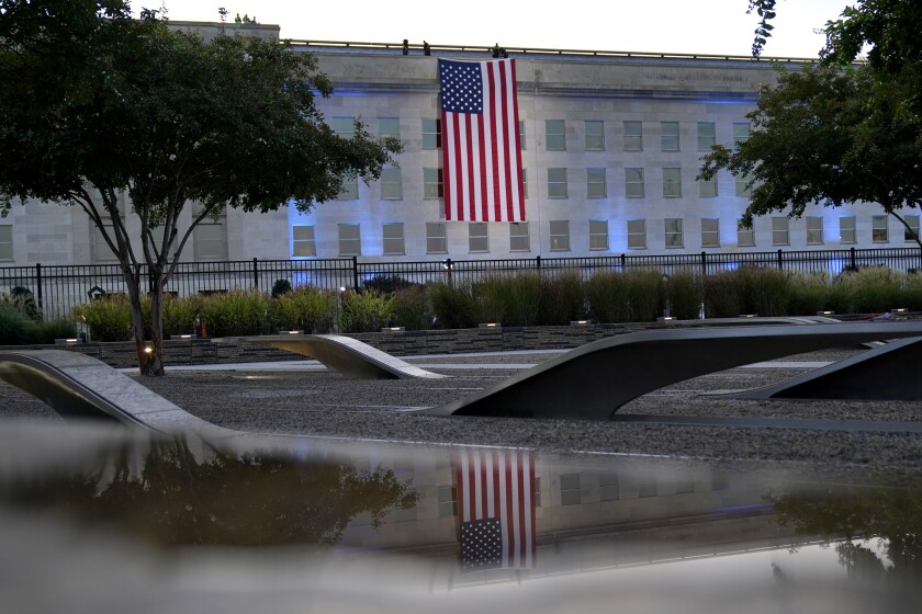 A U.S. flag hangs facing downward on the side of a government building.