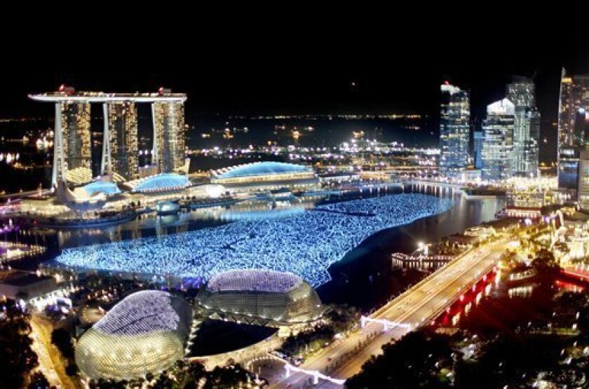 In this photo taken on Friday, Dec. 31, 2010, the financial skyline is lit while the newly opened Marina Bay Sands casinos, left, tower over the bay area as they await New Year's day countdown. Singapore's two huge casino resorts, Marina Bay Sands and Resorts World Sentosa, which together cost more than $10 billion to build, are the crowning jewels of a decade-long effort to diversify the island's economy toward services such as tourism and away from low-end manufacturing. The casinos have created more than 20,000 jobs, helped attract record visitors and fueled 14.7 percent economic growth last year, likely the second-highest in the world behind Qatar, the Trade and Industry Ministry said Monday, Jan. 3, 2011. (AP Photo/Wong Maye-E) (AP Photo/Wong Maye-E)