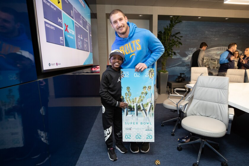 Chargers' defensive end Joey Bosa presents Super Bowl tickets to Caleb Jones-Moreno, who is battling cancer.