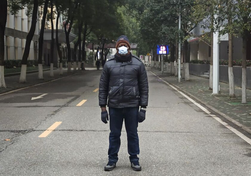 Khamis Hassan Bakari of Tanzania stands in a deserted street in Wuhan, China. Bakari is among more than 4,000 African students in the city of 11 million, which has been locked down by authorities trying to contain the coronavirus.