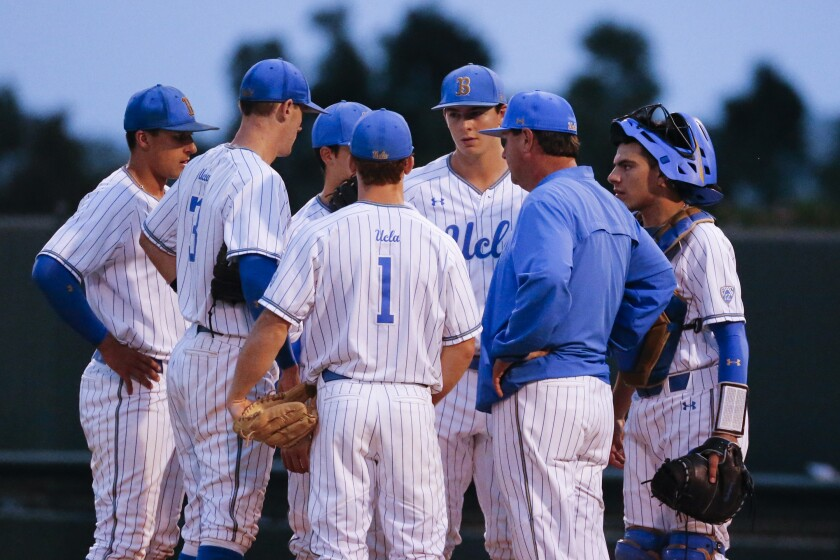 UCLA head coach John Savage talks to his team during an NCAA college baseball tournament super regional game in Los Angeles.