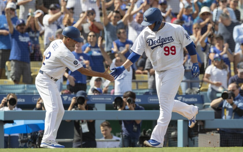 Dodgers pitcher Hyun-Jin Ryu is congratulated by third base coach Dino Ebel after hitting a solo home run.