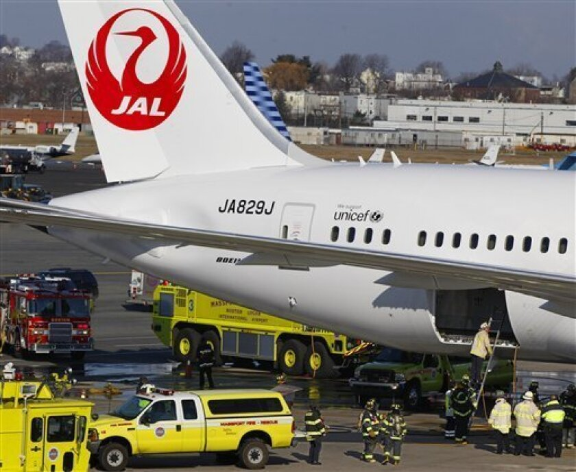 FILE - In this Jan. 7, 2013, file photo, a Japan Airlines Boeing 787 jet aircraft is surrounded by emergency vehicles while parked at a terminal E gate at Logan International Airport in Boston as a fire chief looks into the cargo hold. Federal regulators have approved a Boeing plan to redesign the