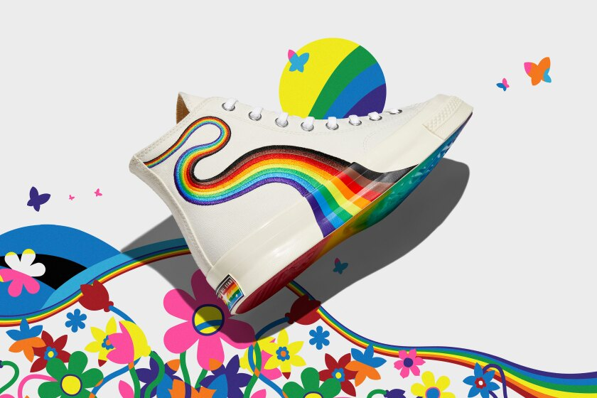 Photo of white Converse high-tops with a rainbow curling down the side.
