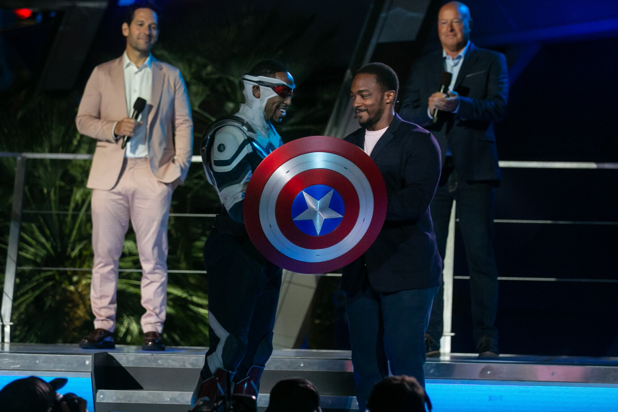 A smiling Anthony Mackie hands a Captain America shield to a Disney actor as Paul Rudd and a Disney executive look on.