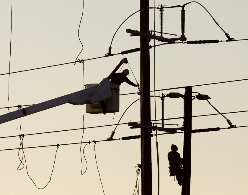 A San Diego Gas & Electric lineman works on a power line.
