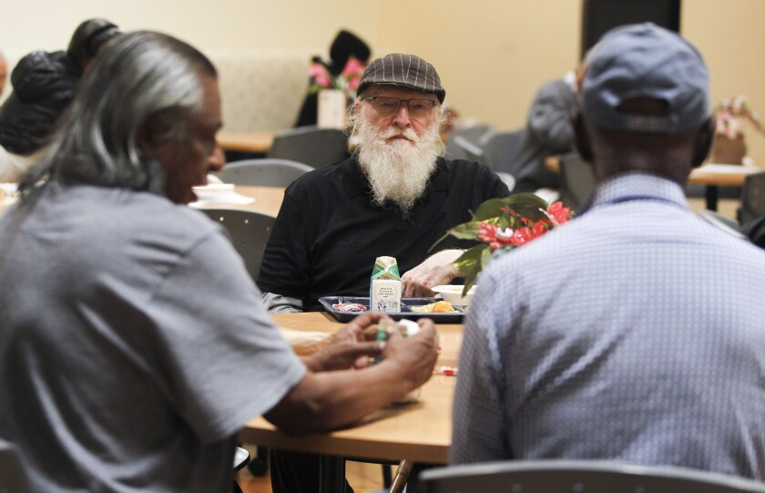 Jap Hari Khalsa, 77, center, sits with Robert Martinez, 60, left, and Floyd Flagg Sr., 83, during lunch at the Gary and Mary West Senior Wellness Center on Tuesday, October 15, 2019 in San Diego, California.
