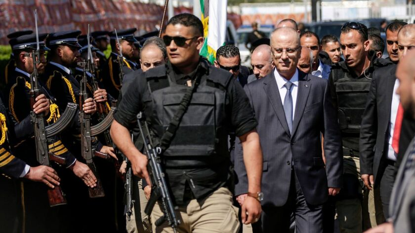 Palestinian Authority Prime Minister Rami Hamdallah, escorted by his bodyguards, is greeted by police forces of the Islamist Hamas movement upon his arrival in Gaza City on March 13.