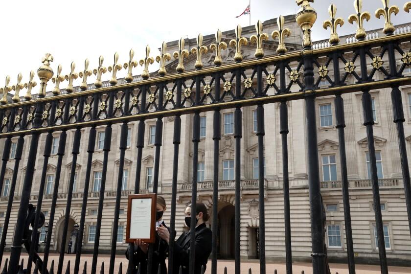 Una bandera de la Unión ondea a media asta mientras personal coloca un anuncio oficial de la muerte del príncipe Felipe