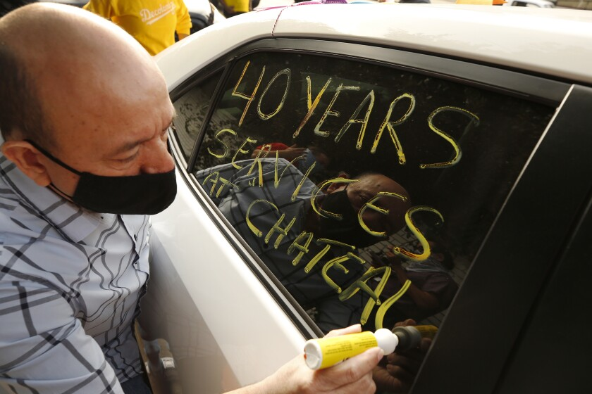 """A man writes on the window of a car: """"40 years serving at Chateau"""""""