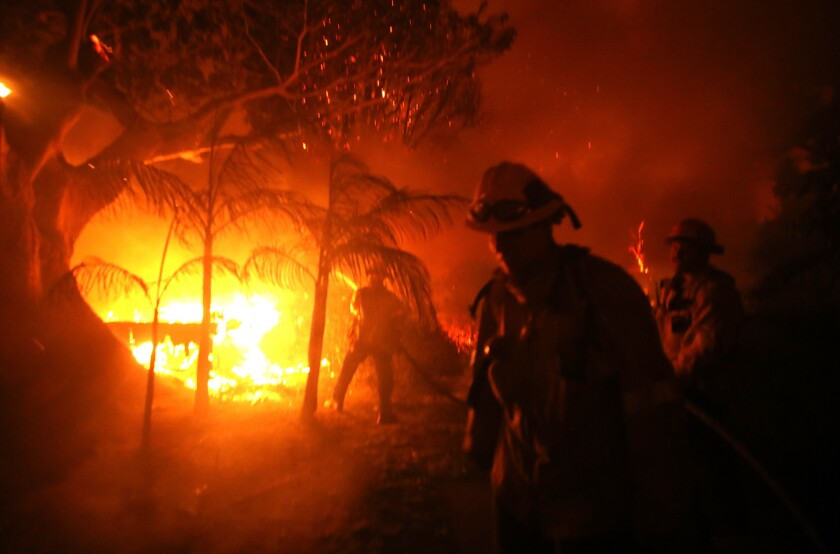 Firefighters work to save a home on Dume Drive in Malibu as the Woolsey fire rages