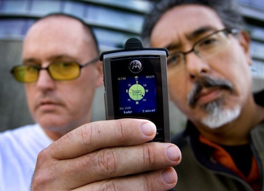 The Transborder Immigrant Tool, a cell phone with a GPS application, is demonstrated by Brett Stalbaum, left, a lecturer at UCSD, and UCSD Associate Professor Ricardo Dominguez, right, the principal investigators.