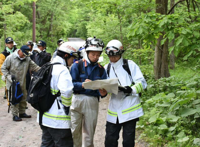 Rescuers serach for a 7-year-old boy who is missing in a Japanese forest in Nanae town, on Hokkaido, the northernmost of Japan's four main islands Monday, May 30, 2016. He has been missing since late Saturday afternoon after his parents reportedly made him get out of the car as punishment. (Kyodo N