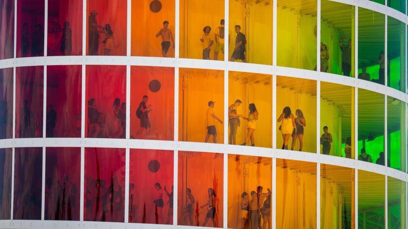 INDIO, CALIF. - APRIL 19: Festival attendees walk inside the Spectra, an secen story art installatio