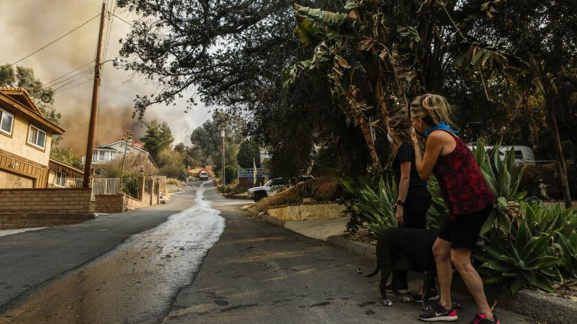 Ashley Bemis, a San Clemente woman is accused of making up a firefighter husband to scam people into giving her donations. Pictured above, residents watch the Holy Fire, which is the fire Bemis claims her husband was fighting.