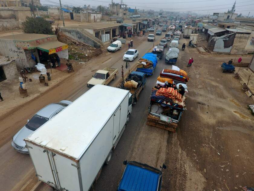 Syrian families drive through the village of Hazano, about 20 kilometers northwest of the city of Idlib, towards the Syrian-Turkish border as they flee from the assault led by government forces and their allies.