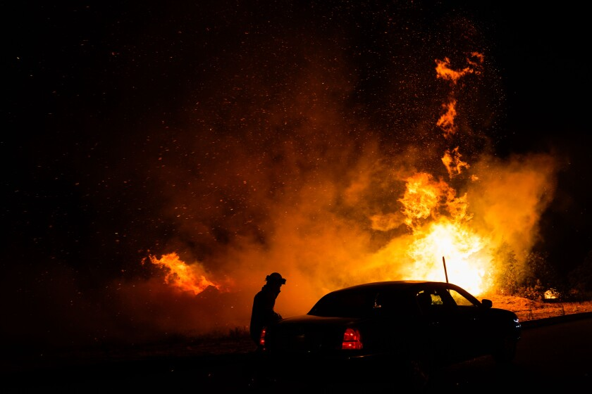 The Creek fire jumps California Highway 168 on Tuesday in Fresno County.